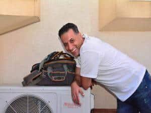 אברהם מור טכנאי מזגנים אלקטרה נשען על מנוע מזגן